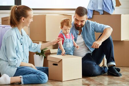 Kid wear denim overall, blonde woman wear blue shirt, jeans and white socks and bearded dark-haired man smile and play with box. Key on box. Background moving boxes