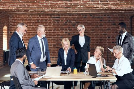 Group of eight business people wear office suits brainstorming together, share ideas, talk in meeting room with brick walls. Each move. In centre table on which laptops, glasses of water, paper notes
