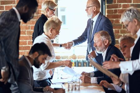 Group of businessmen at table in office. Camera focused on two of them shaking hands Reklamní fotografie