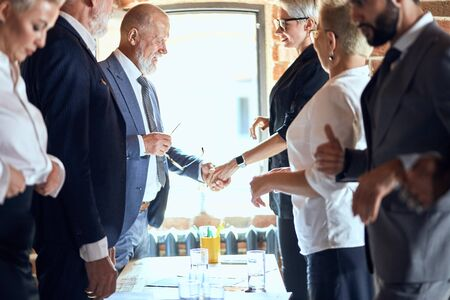 Group of businessmen at table in office. Focuced on shaking hands caucasian man and woman