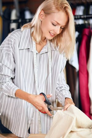 cheerful abeautiful blonde tailor using scissors at work, lifestyle, free tinme, spare time Stok Fotoğraf