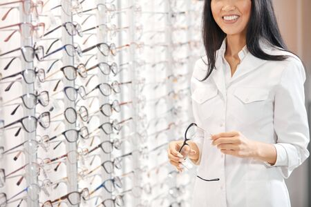 Asian woman in white medical uniform holding glasses, recommending customers to buy them. close up cropped photo