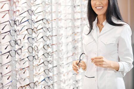 Asiatische Frau in weißer medizinischer Uniform, die eine Brille hält und Kunden empfiehlt, sie zu kaufen. Nahaufnahme ausgeschnittenes Foto Standard-Bild