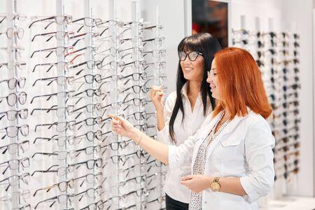 Zwei positive Frauen, die es genießen, eine Brille zu wählen, während sie neben einem Glasregal mit vielen Gläsern, Glück, Kopierraum stehen