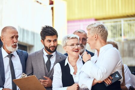 Two caucasian bearded men in suits and two caucasian woman with short white haircut, red lips wear white office shirts discuss project outdoor