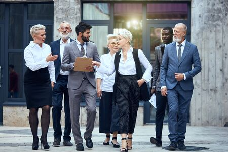 Group of businessmen dressed in stylish office clothes discuss project and move in street