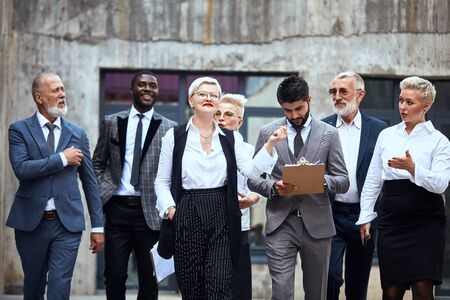 Six caucasian and one african businessmen dressed in stylish office clothes move energetically in street