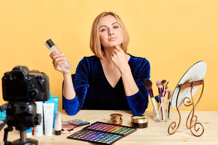 Attractive self-confident woman holding primer, describing its benefits, presenting new cosmetics line, shooting video review for blog, gazing in camera, sitting at dressing table in studio.
