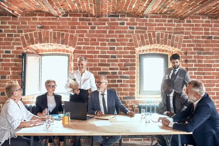 Six caucasin and one african businessmen wear different stylish suits discuss upcoming project at table in office brick walls Stockfoto