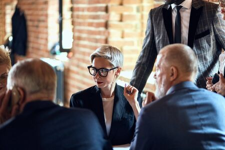 Focused on blonde caucasian woman in glasses between backs of two men