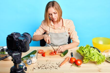 Front view of cute blonde woman cutting raw tomatoes for spicy sauce, cooking special dinner for her big family, using fresh vegetables and organic ingridients. Healthy food and culinary concept. Stockfoto