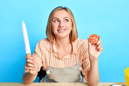 Close up portrait of beautiful blonde housewife thinking what to cook for dinner, looking aside, smiling broadly, holding large sharp knife in one hand and sliced fresh tomatoe in the other.