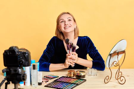 Smiling cheerful beauty blogger girl holding bunch of cosmetic brushes, representing makeup products for her online shop, looking upwards with delightful expression, has great mood, enjoys her job. Stockfoto
