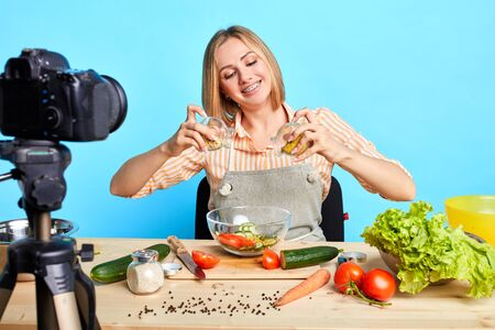 Joyful pretty professional female chef shooting cooking process for her culinary show, loves her job, has delightful face expression, making special dietary vegetarian meal with low calories. Stockfoto