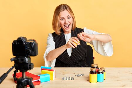 Cheerful pretty pharmaceutical company representative recording video presentation for new health care products, trying to open firmly closed bottle with funny face expression, has playful mood.