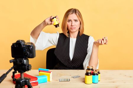 Isolated view of sad blonde nutritionist showing empty bottle with her health supplement, forgot to buy new one, purses lips and frowns, displeased and upset expression. Studio shot. Stockfoto