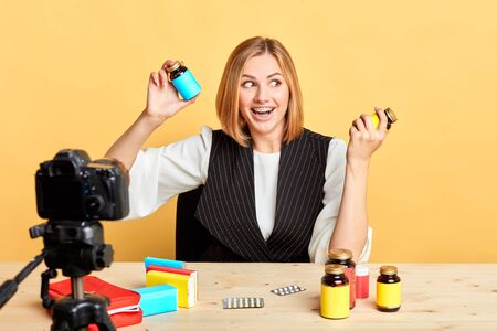 Cheerful pretty female dietitian holding two bottles with food supplements and vitamins, having fun, joking and laughing while recording new podcast for her health and beauty blog, looking aside.