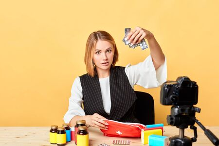 Isolated view of young female blogger with medical degree showing must have pills and supplements for travel first-aid kit, shooting healthcare video for her personal blog, sitting in home studio.