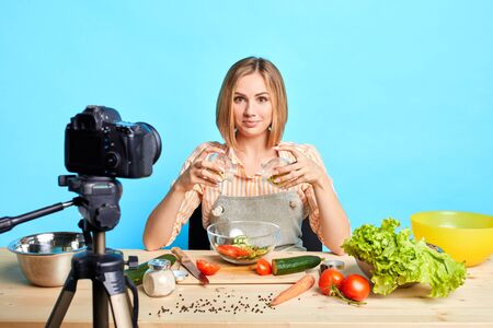 Talented female chef created new recipe, making dish in front of camera, recording online cooking tutorial, posing at table with fresh ingredients, using raw lush vegetables and spices.