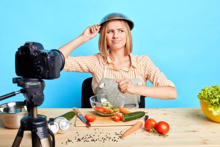 Uncertain female chef looks aside with doubts, forgot recipe for new dietary fresh salad, feels disappointed, needs to search information in internet to continue shooting video for her culinary blog.