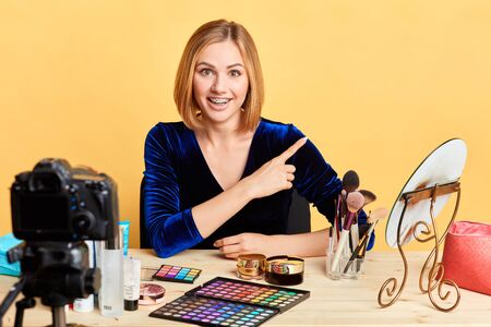 Cheerful young woman with blonde hair, looking in camera with broad smile with dental braces, presenting makeup and cosmetics, pointing aside, free copy space for your text and advertisement.