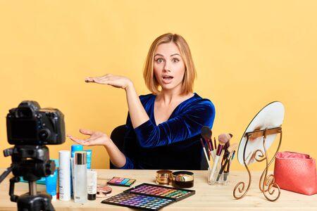 Suprised famous female blogger with wide opened eyes shapes height of gift box with both hands, gestures against copy space, excited emotions, posing over light yellow background, isolated shot.