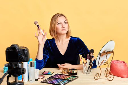 Attractive glamourous female model posing for makeup advertisement sitting at table full of cosmetics products, looking aside, holding brush for powder. E-commerce and networking concept.