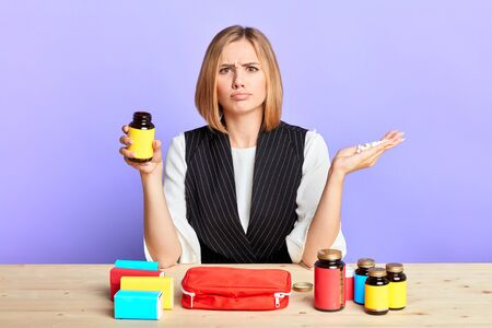 Uncertain blonde woman poses with clueless expression in front of table with lots of different drugs, frowns face in doubts, in one hand unlabeled bottle with vitamins and other is full of pills. Stockfoto