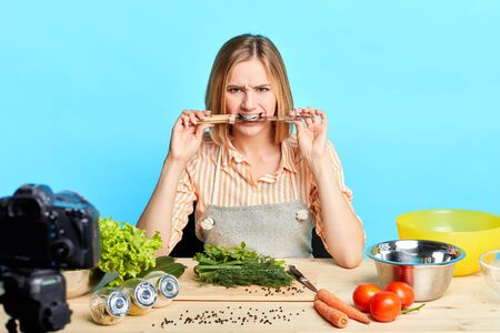 Female food blogger looks at camera angrily, holds and clenches between her teeth large knife, failed to cook salad by new recipe, feels disappointed and frustrated, needs new content for her blog.