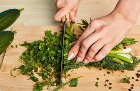 Cropped shot of womans hands chopping scallions and parsley on wooden cutting board with large knife, prepares healthy vegetarian salad for dinner. People, food and cooking concept Stockfoto