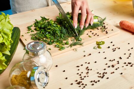 Top view of unrecognizable womans hands cutting parsley and scallions for green sauce, preparing special dinner for her lovely husband, cooking healthy and tasty meal. Culinary concept. Stockfoto