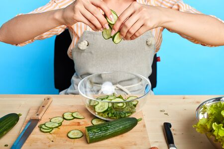 Cropped shot of unrecognizable woman in apron and casual shirt with stripes, preparing fresh smoothie, using raw organic sliced cucumbers and parsley, wants to lose some weight. Healthy food concept.