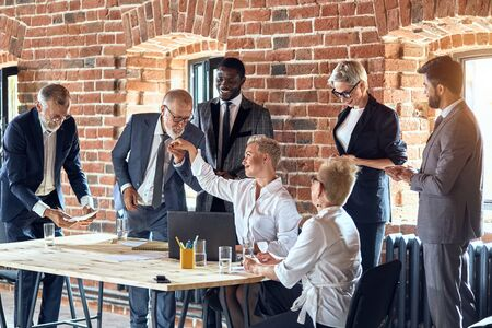 Creative director blond woman wear white office shirt sit at table. Colleagues smile, congratulations the completion of successful transaction. Man near wear blue stylish suit kiss hand