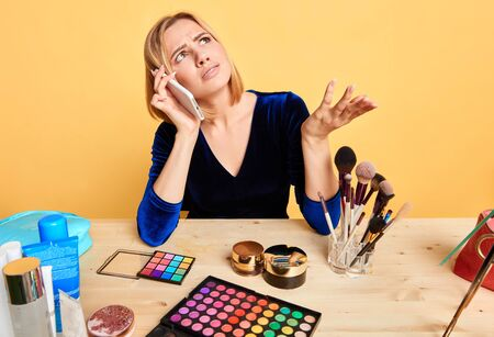 Portrait of dissatisfied young blonde female model talking by smartphone while making makeup and beauty routine, having unpleasant expression, frowning face, arguing and disagreeing, looking aside. Stockfoto