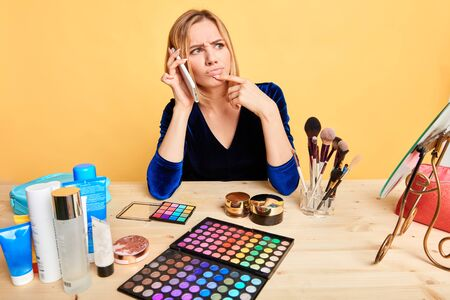 Young attractive female makeup artist waiting client who is being late, calling her impatiently, nervous and unpleasant expression, frowning, touching chin with index finger, isolated view.