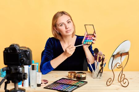 Charming young woman blogger working on content for personal beauty blog, shooting new video, sharing makeup tips with her followers via social networks. Advertising and networks concept. Stockfoto