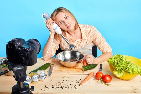 Popular food blogger girl holding hand blender, looking at camera with gentle smile, ready to start shooting new video content for her cooking blog, going to make healthy vegetarian dish.