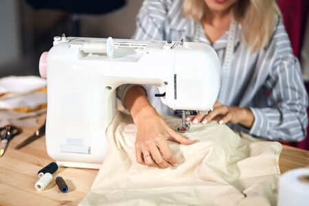 girl sewing with a professional machine, embroiders on white fabric using both sides of the material. Concept of: Factory, Home. close up cropped photo