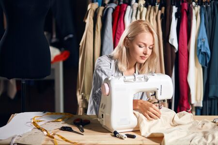 Young blonde serious needlewoman at studio working with sewing machine. close eup side view photo.