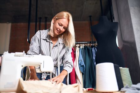 young designer concentrated on making clothing indoors. close up photo