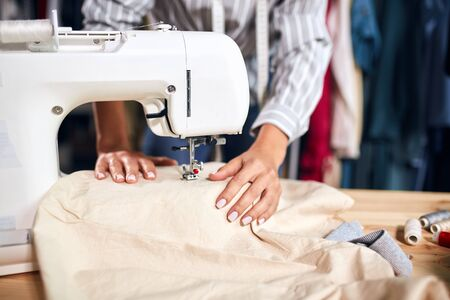 close up cropped photo.hardworking talented creative tailor mending cusstomers clothing. working process.