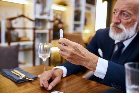Elegant greybeard senior man buy electronic sigarette, testing e-cigarette. Stop smoke in social places 스톡 콘텐츠