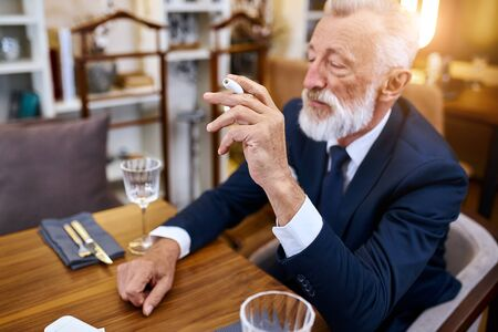 Elegant senior man in suite smoke heat-not-burn tobacco product technology sit in restaurant, holding cigarette in right hand 스톡 콘텐츠