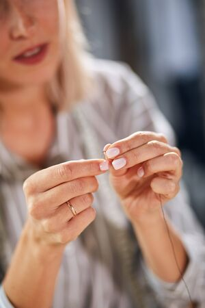 woman threading needle at home, focus on palms, hands. blurred background, sewing tool. equipment. close up cropped photo Stock Photo