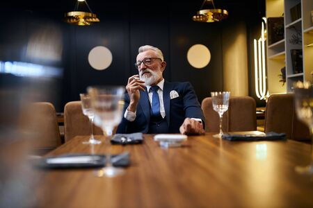 Senior grey-haired man holding and smoke e-cigarette in rich restaurant . IQOS, modern technologies, stop smoke 스톡 콘텐츠