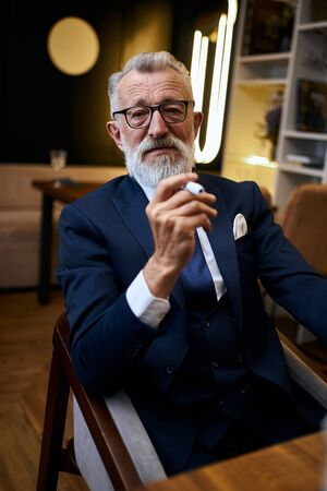 Handsome grey-haired senior man in glasses in suit smoke IQOS in restaurant, explore cigarette holding in hands