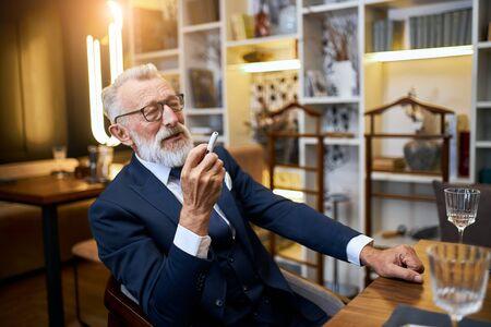 Attractive older man enjoys smoking electronic cigarette in restaurant. Senior man using e-cigarette, IQOS