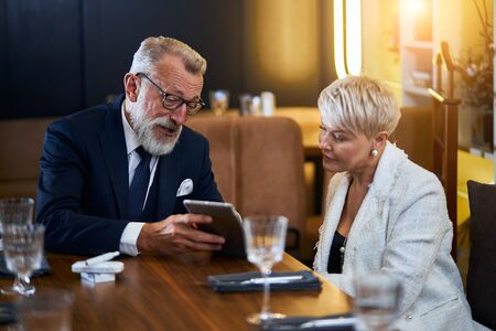 Beautiful senior couple in love speaking in rich restaurant, man show smith interesting in laptop. Modern couple