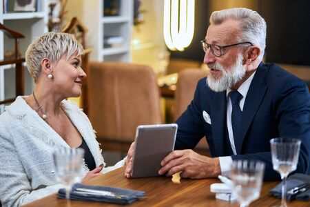 Joyful, cheerful, mature couple in love having time at restaurant while chatting and looking at each other. Senior man show something in tablet