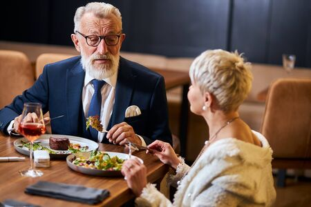 Pretty lady and elderly grey haired man in tuxedo having friendly conversation in restaurant. Colleagues after work discuss and eat Banco de Imagens